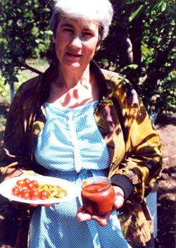 Elizaveta Gavriliuc displays fresh tomatoes from her plot and jam she has made from her fruit.